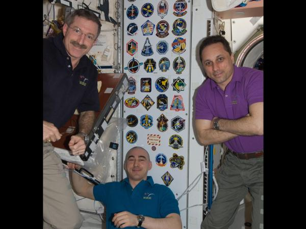 International Space Station - Expedition 30 Crew Members Pose With Shuttle Insignia